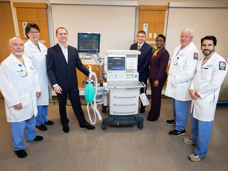 Group of people posing with anesthesia machine.
