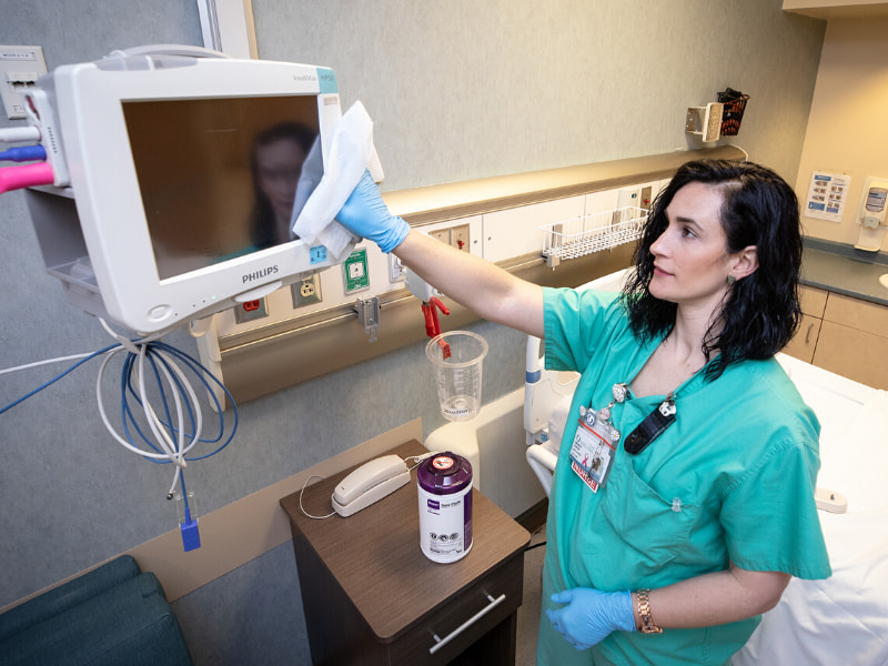 Nurse wears gloves and uses a disinfectant wipe to clean equipment.