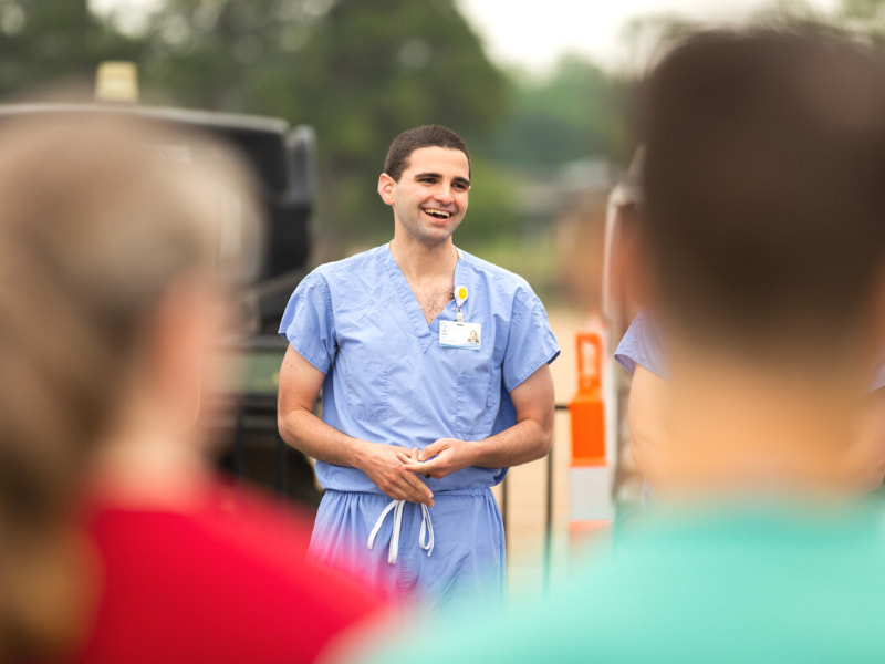 Subhi Younes, School of Graduate Studies in Health Sciences student, shares a laugh with other employees and volunteers after a safety briefing at the fairgrounds.