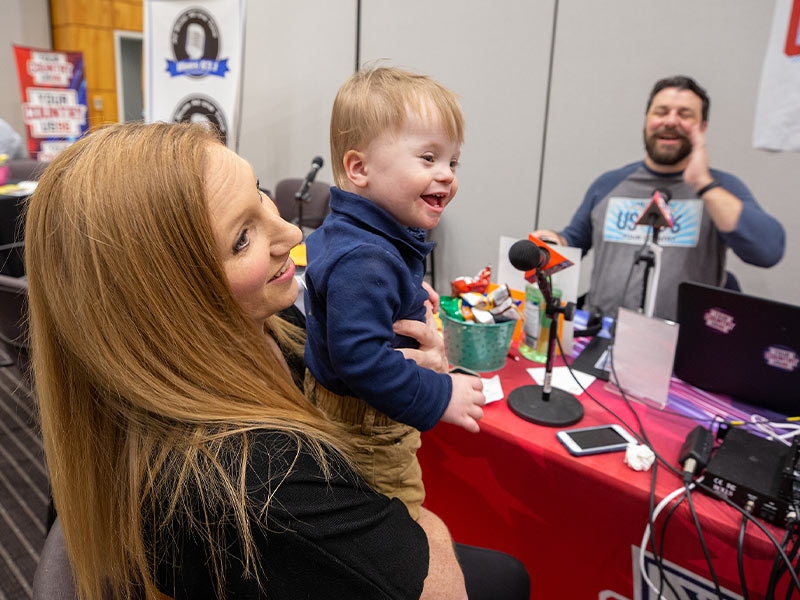 Children's of Mississippi patient Ward Phillips of Madison smiles with mom Abbey during their interview with US 96.3 during the 19th annual Mississippi Miracles Radiothon.