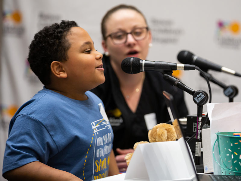 Deuce Bloodsaw speaks on live radio as mom Nikki Cohran, a Children's of Mississippi nurse manager, looks on.