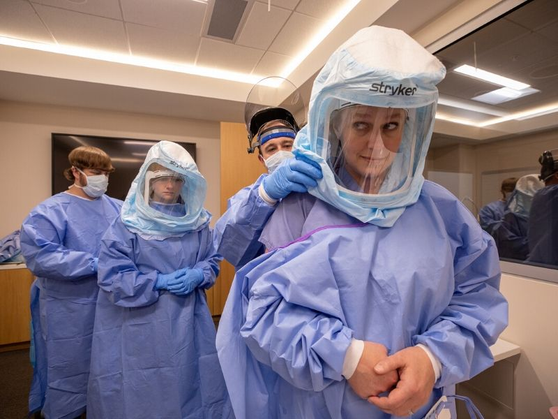 John Carter, left, MICU nurse, helps Jessie Harvey, second from left, assistant professor of medicine, pulmonary, don protective gear while J. D. Chisolm, second from right, MICU nurse, does the same for Kelly Jones, respiratory therapy supervisor, during a pilot training session in the Simulation Center.