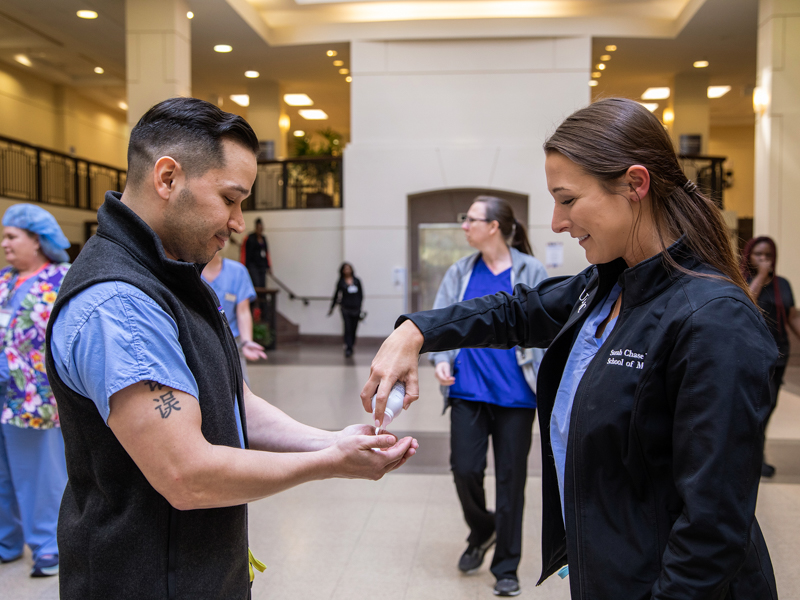 First-year medical student Sarah Dulske, right, offers hand sanitizer to Zeke Gonzalez, chairman of the COVID-19 Student Response Coordination Team. Dulske is a team leader in the group.