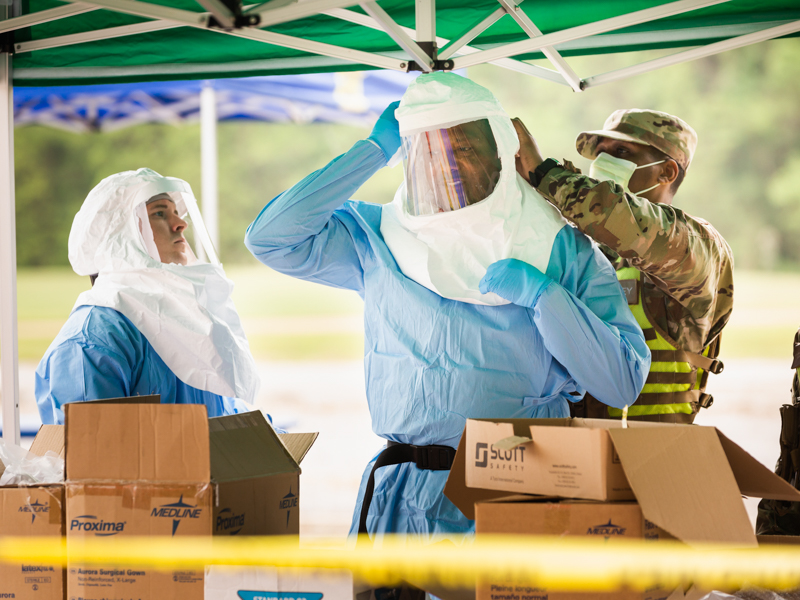 UMMC employees and students put on personal protective equipment fo COVID-19 sample collections April 8 at Traceway Park in Clinton.
