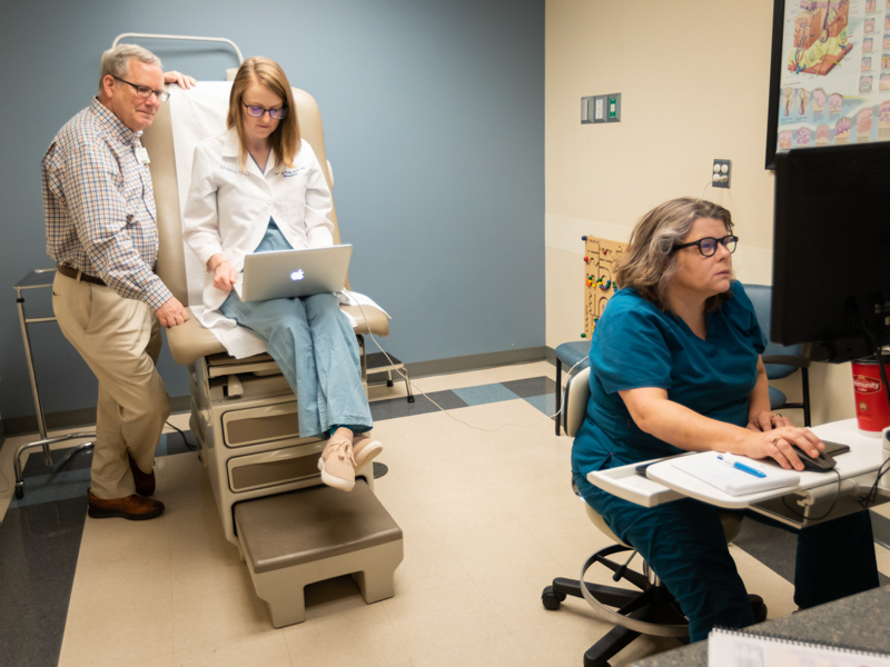 Dr. Robert Brodell, UMMC dermatology chair, joins Dr. Caitlyn Trotter Reed, center, dermatology house officer, and Tracy Breeden, nurse, to conduct a telehealth video conference with a patient.