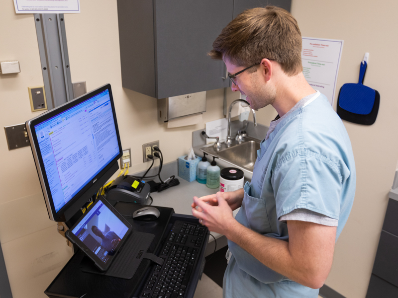 Dermatology Resident Dr. Mark Braswell sets up his telehealth equipment in preparatoin for patient videoconferencing.