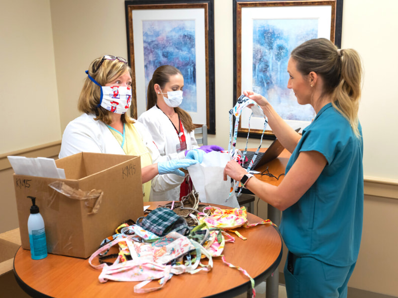 Registered Nurse Heidi Johnson, left, gives a mask to Registered Dietitian Lauren Page, right.