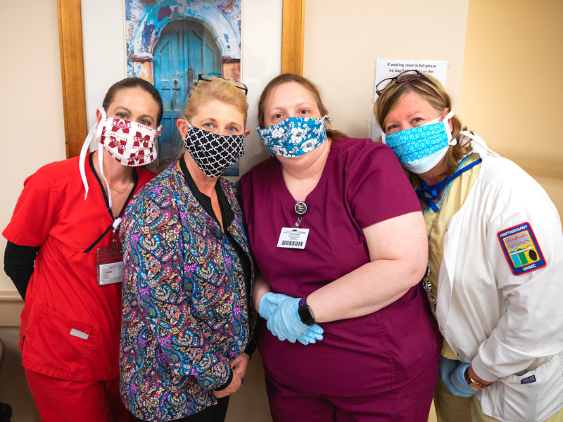 Modeling homemade masks with vibrant patterns are, from left, Emily Smith, ophthalmic technologist; Leigh Kelly, ophthalmic surgery technician; Chynna Martin, ophthalmic technician; and Heidi Johnson, nurse.