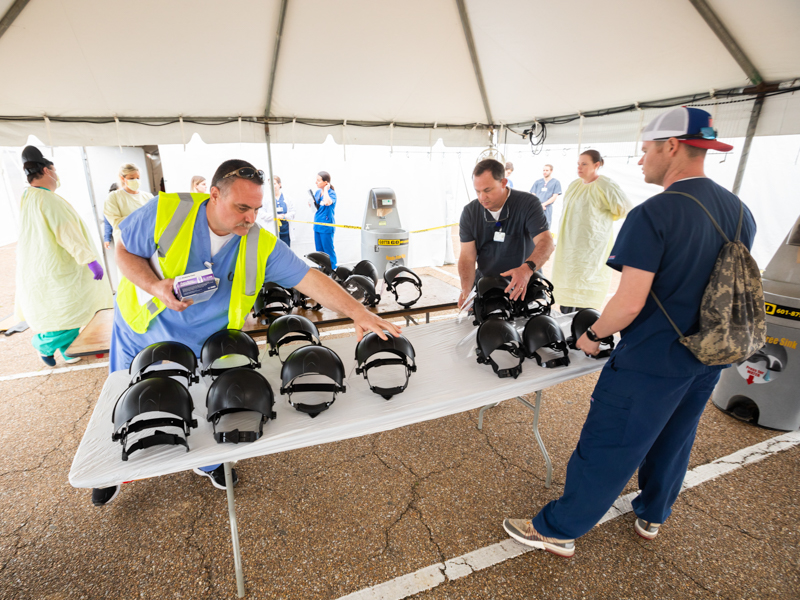 Left to right, Thomas Douglas, RN, Thomas Moak, polysomnographic tech, and Aaron Arnold, polysomnographic tech, sanitize face shields at the fairgrounds testing site.