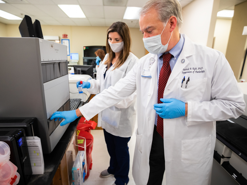 Dr. Patrick Kyle, a toxicologist and associate professor of pathology, and medical laboratory technician Ashleyanne Westbrook perform testing on COVID-19 specimens.
