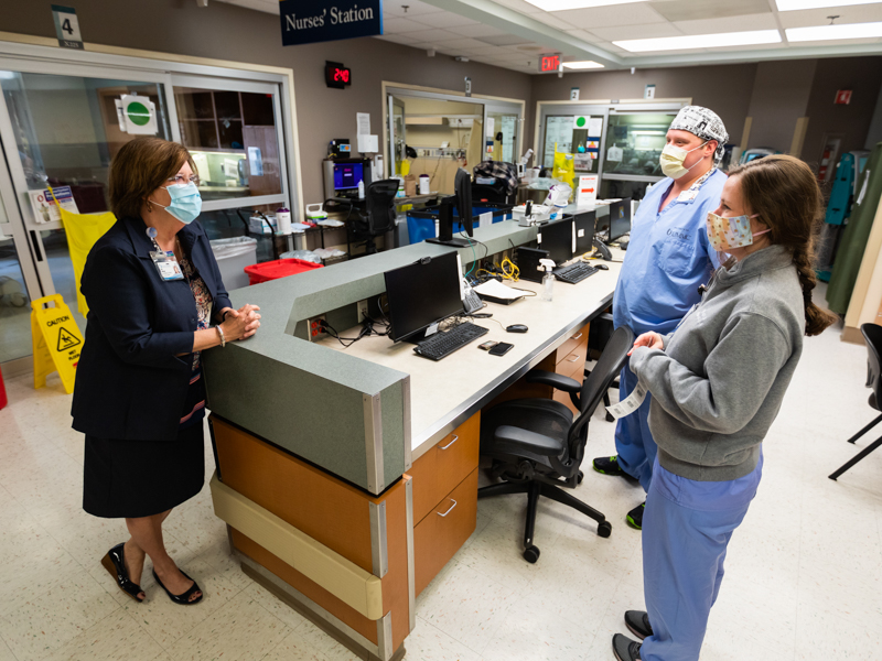 Terri Gillespie, UMMC chief nursing executive and clinical services officer, checks in with registered nurses William Parish and Maggie Luke while making rounds in the Medical ICU, where COVID-19 patients receive care.