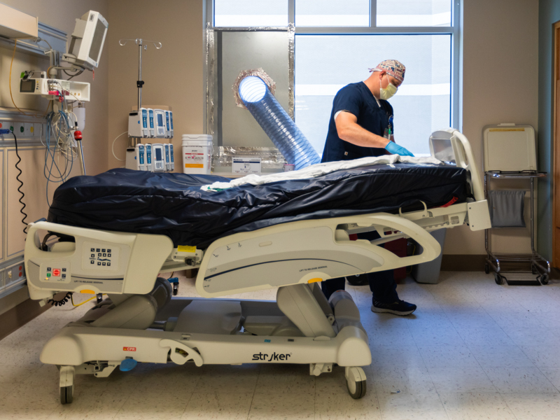 Mike Henrickson, a MICU registered nurse, prepares a room for the next patient.