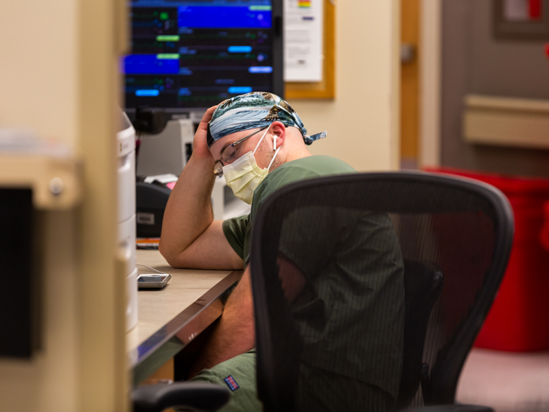Registered nurse Kevin Marchant takes a moment to breathe in the MICU, where very ill COVID-19 patients receive care.