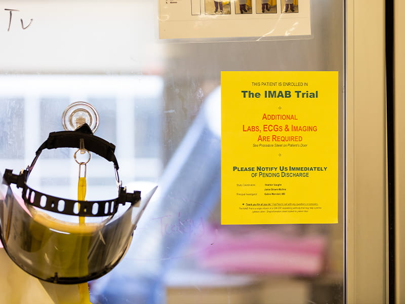A sign hanging from a COVID-19 patient room on the medical ICU lets caregivers know that person is taking part in one of UMMC's clinical trials.