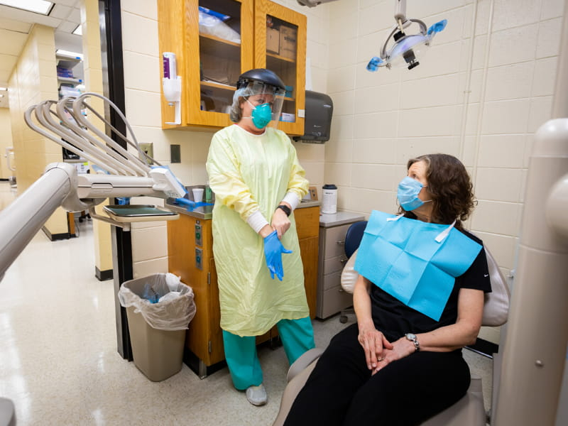 Tiffany Tompkins, dental hygienist, dons her personal protective equipment before Betty Vinson's routine cleaning.