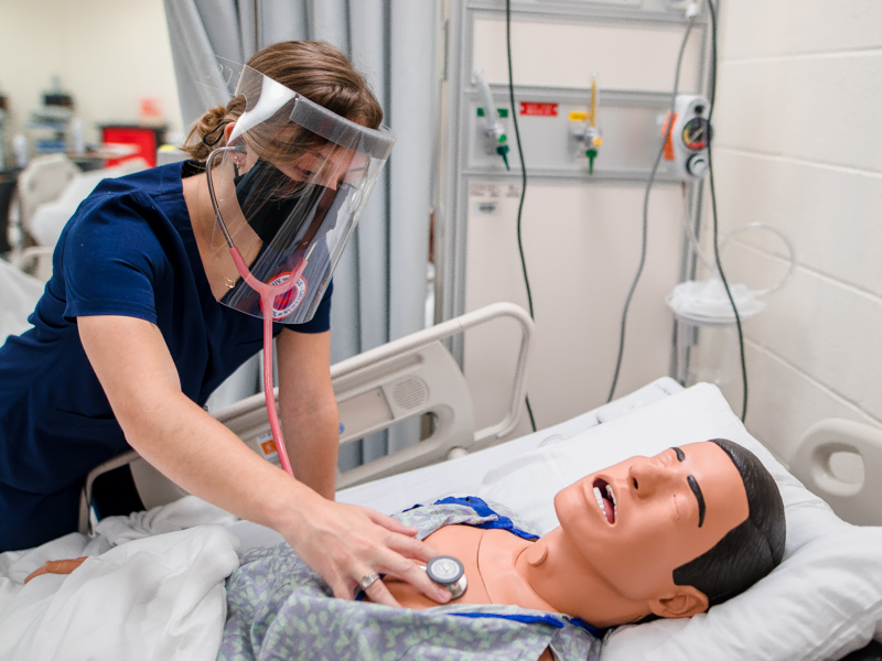 Alexandra Tzotzolas, a School of Nursing student, wears a face shield and maintains her distance from other classmates while she listens to the heart and lungs of a mannequin in the SON's simulation lab. Students in all seven UMMC schools who venture onto campus this fall will have to adhere to specific safety guidelines.