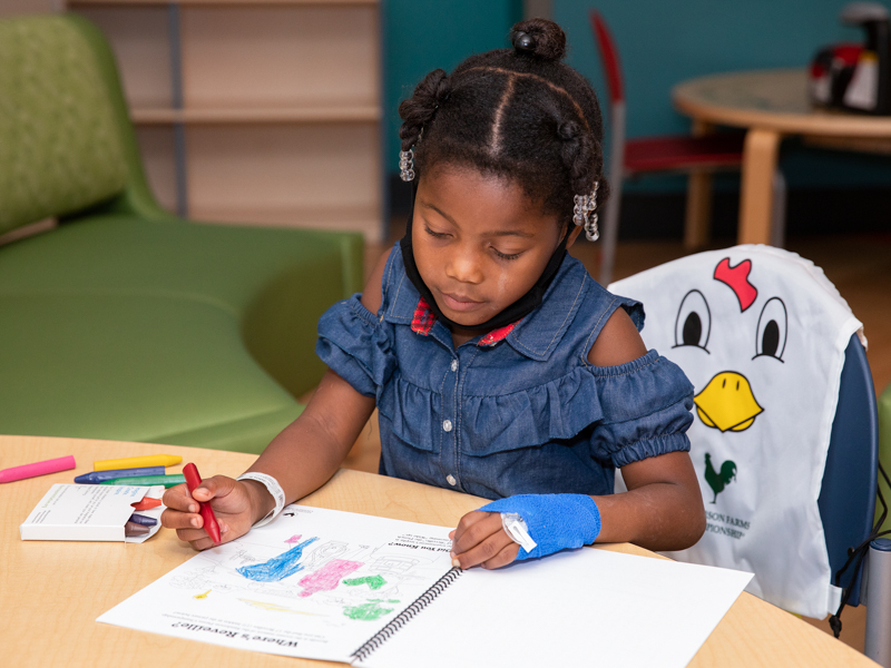 Jakia Jones of Vicksburg, a Children's of Mississippi patient, colors a page in the Sanderson Farms Championship activity book included in the tournament backpack given to patients.