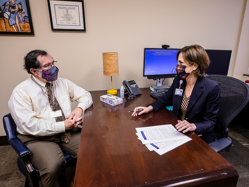 Dr. Roy Duhe, left, meets with Dr. Sara Gleason, professor of psychiatry and human behavior, after becoming one in eight COVID-19 survivors last spring who, within six months of testing positive, were diagnosed with a mental disorder for the first time.