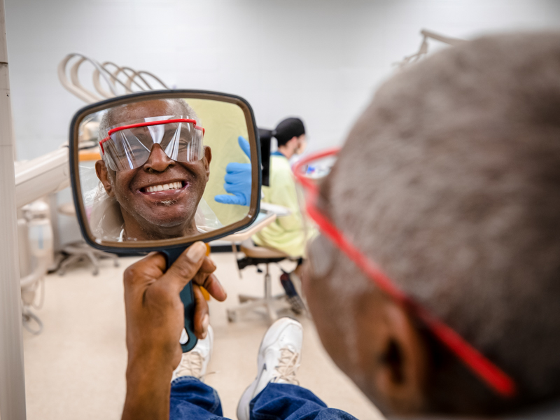 Wilbert McGee inspects his new dentures crafted by Trent Johnson, School of Dentistry student.