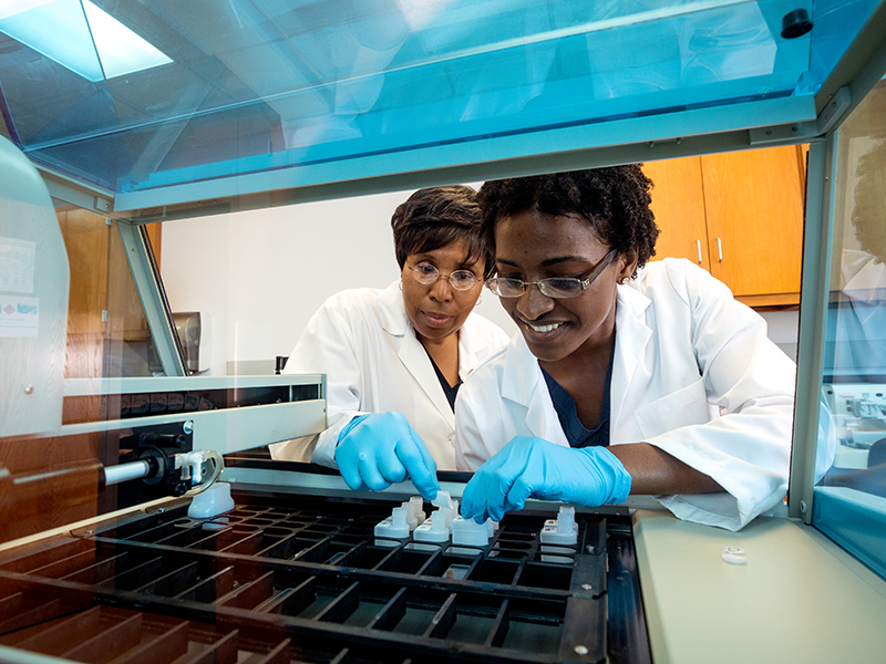 Bevilyn Perkins. left, instructor in medical laboratory science and educational coordinator of the Histotechnology Program, shows how some of the new state-of-the-art lab equipment works to Aiesha Norwood, histotechnology student.