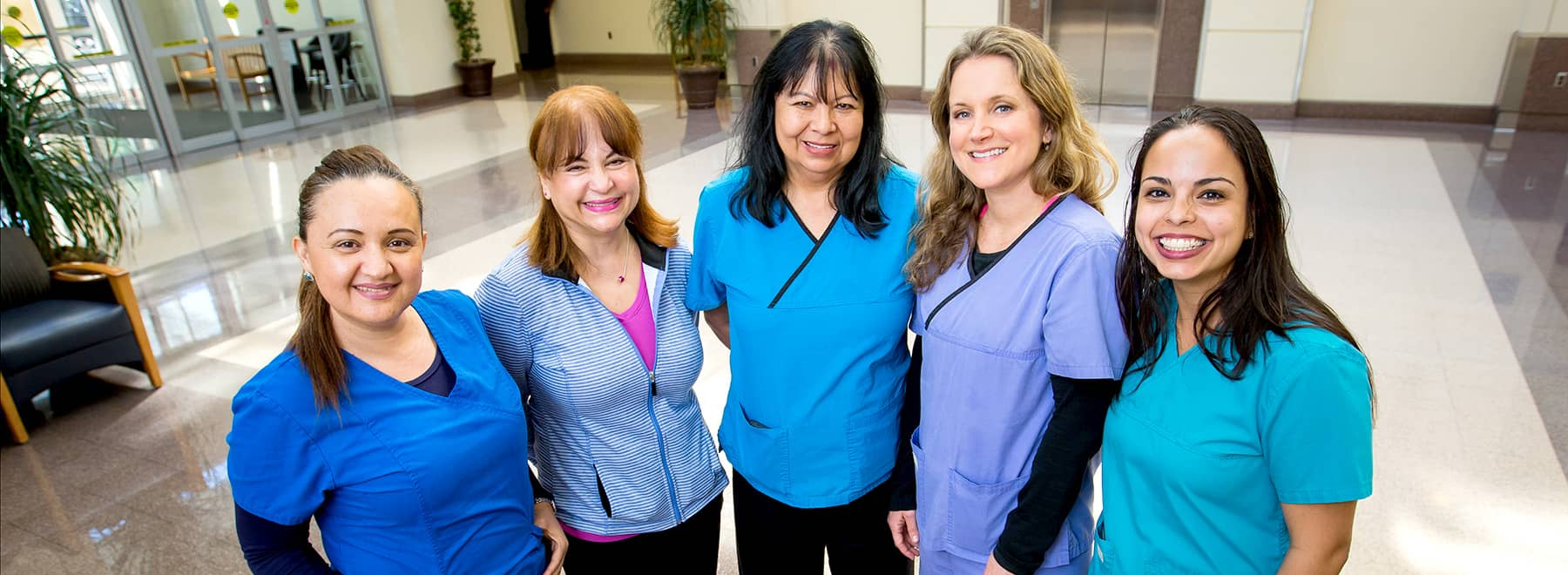 Group of female medical interpreters pose in a UMMC lobby.