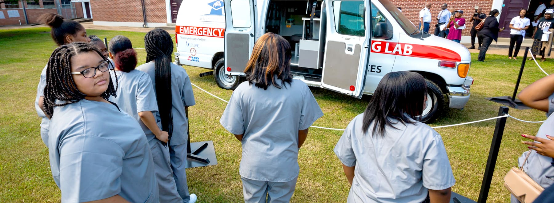 Female Lanier high school students stand in line to see a retired ambulance that was refitted to serve as a stationary simulation lab.