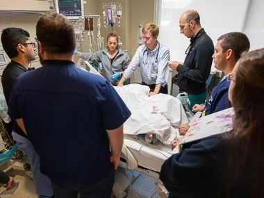 Medical team circles the bed of a hospitalized patient