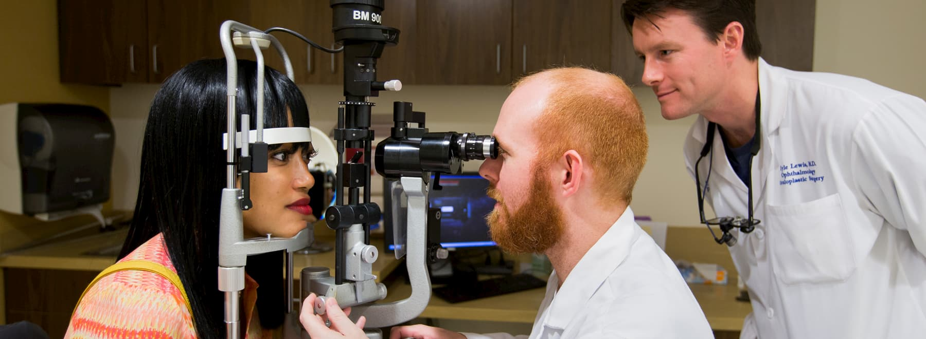 Two ophthalmologists examine a patient