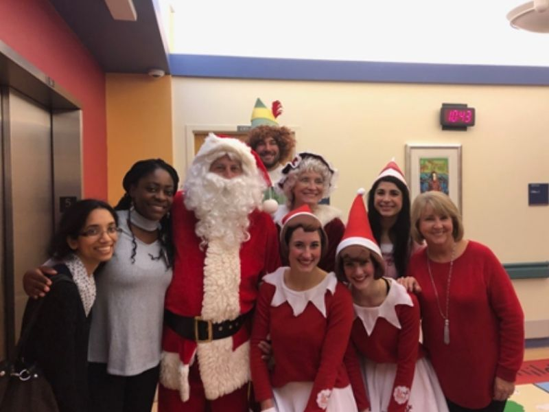 Students dressed as elves pose with Santa.