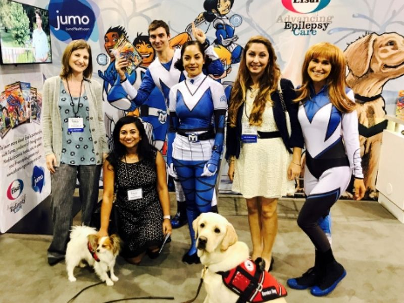 Student stand with service dogs handled by people dressed as super heroes.