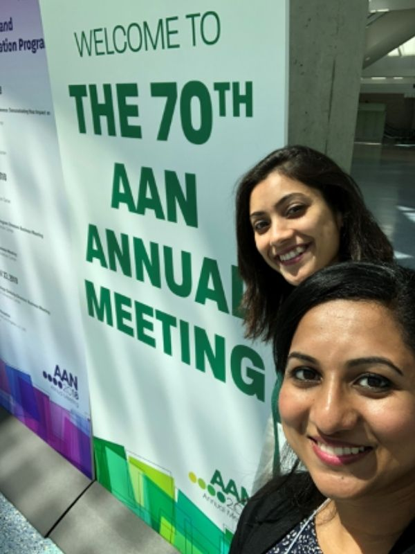 Two students pose in front of a sign denoting the 70th AAN Annual Meeting.