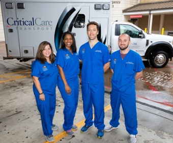 Four pediatric emergency fellows stand in front of an ambulance.