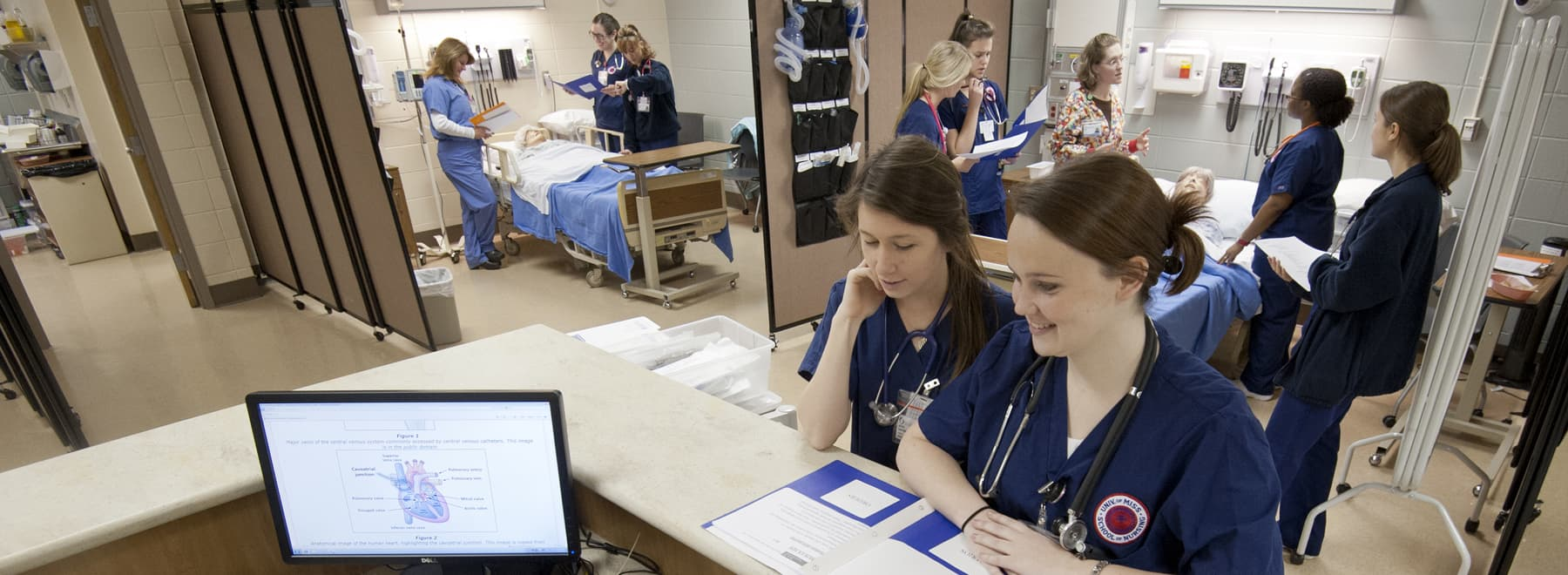 Two students look over a case while others communicate with faculty at the simulated bedside.